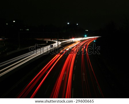 Time exposure photo (30 seconds) with a street at night and automobile headlights of a multiple lane city street and a traffic light, seen at the Autobahn near Auestadion in Kassel, Germany