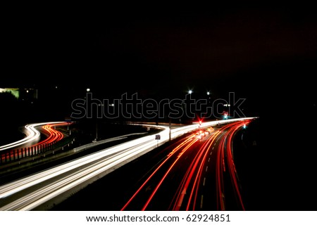 Time exposure photo with a street at night and automobile headlights of a multiple lane city street and a traffic light, seen at the Autobahn near Auestadion in Kassel, Germany