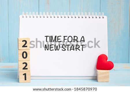 Time for A New Start words and 2021 cubes with red heart shape decoration on blue wooden table background. New Year NewYou, Goal, Resolution, health, Love and Happy Valentine's day concept