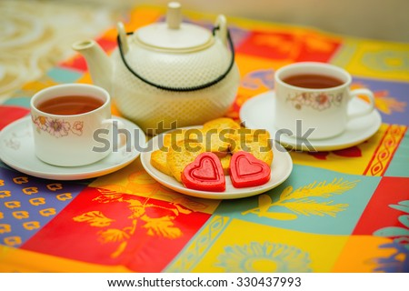 Time for a tea break.  2 cups of hot drink, tasty cookies, heart shaped candies, chocolates on a table.  Date, friends visit, grand mother house, breakfast, waiting for guests, love for tea concept.