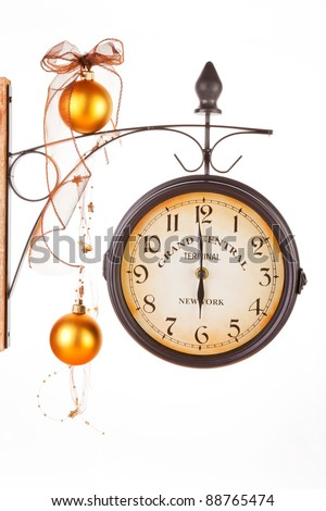 Time for coming together and festive dinner. Traditional classic clock decorated with golden xmas decoration and ribbon.