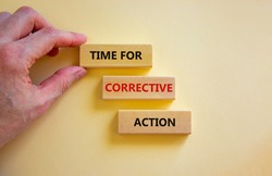 Time for corrective action symbol. Wooden blocks with words 'Time for corrective action' on a beautiful white background. Businessman hand. Business, time for corrective action concept. Copy space.