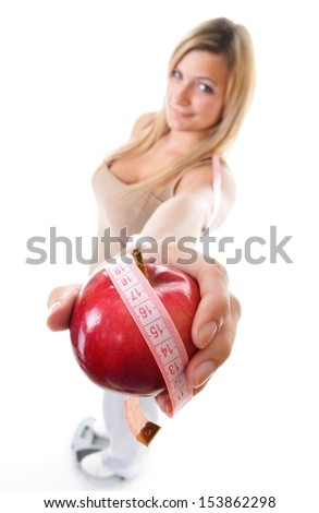 Time for diet slimming. Woman plus size large girl on scale with apple measuring tape - weight loss concept. Isolated on a white background.