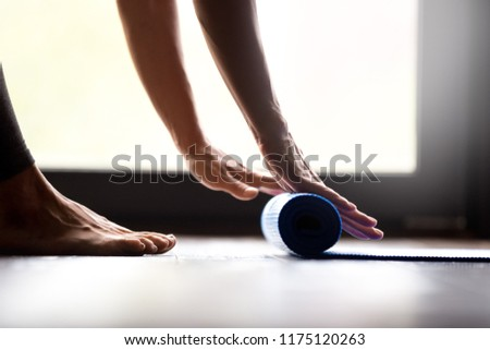 Time for fitness lesson concept. Close up view of fit beautiful young female yogi hands rolling blue color fitness, pilates or yoga mat before or after working out at indoor yoga studio or at home