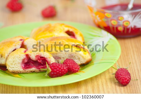 Time for good food: raspberry baking pie on the green plate with red syrup