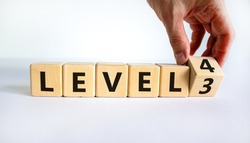 Time for Level 4. Hand turns a cube and changes words 'level 3' to 'level 4'. Beautiful white background. Business and next level concept. Copy space.