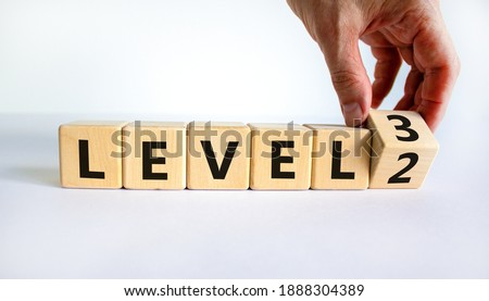 Time for Level 3. Hand turns a cube and changes words 'level 2' to 'level 3'. Beautiful white background. Business and next level concept. Copy space. Stock fotó ©