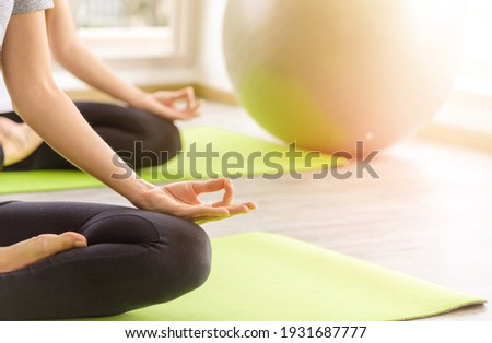 Time for practicing yoga. Two youngs attractive women sitting in Ardha Padmasana exercise, Lotus pose on meditation, closed eyes, wearing sportswear on mat at home. lifestyle concept Stock photo ©