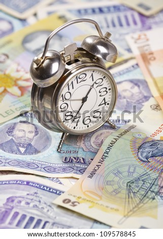 Time for profit. Old alarm clock on stack of euro and romanian banknotes, very old and new ones.