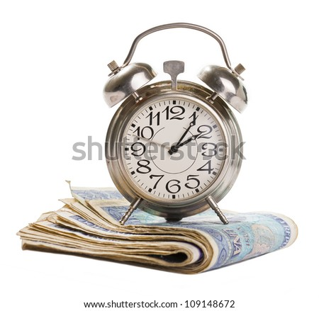 Time for profit. Retro alarm clock on a stack of banknotes isolated on white.