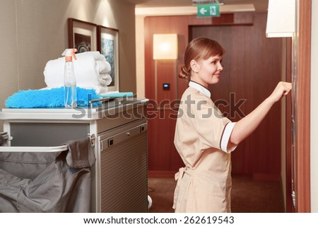 Time for room service. Smiling hotel maid in beige uniform knocking on the hotel room for room service by the maid trolley in the hotel hall