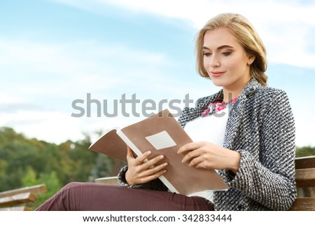 Time for studying. Horizontal shot of a pretty woman reading her notebook studying in the park