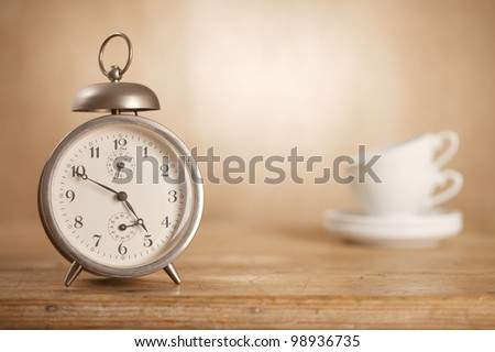 time for tea, retro alarm clock and tea cups, hessian burlap background with uneven light