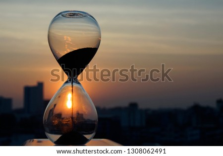 Time is going by in an hourglass with blur city at twilight time