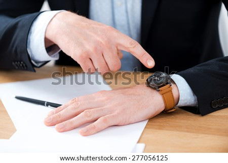 Time is money. Close-up of businessman pointing on his watch while sitting at his working place #277056125