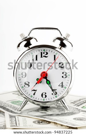Time is money concept. Retro styled alarm clock on the money.