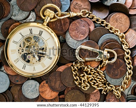 Time is money conceptual closeup of gold pocket watch with a background of United States coins. Pennies,nickles, dimes