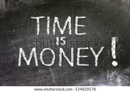 Time is money handwritten with white chalk on a blackboard