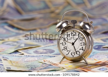 Time is money. Old alarm clock on large amount of banknotes - very old and new romanian banknotes and euros.