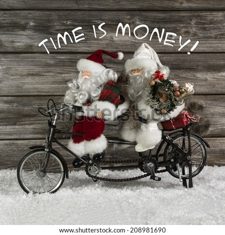 Time is money -  santa claus team in hurry for buying christmas presents. Funny photo in vintage style with an old tandem bike of tin.