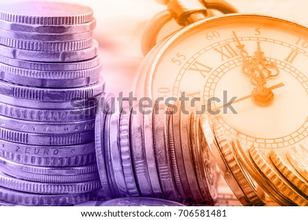 Time is money, time value of money concept : Coins and vintage brass pocket watch, idea of time which is a valuable commodity or resource and it's better to do work or things as quickly as possible. #706581481
