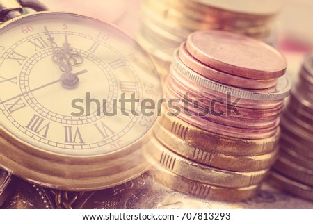 Time is money, time value of money concept : Coins and vintage brass pocket watch, idea of time which is a valuable commodity or resource and it's better to do work or things as quickly as possible. #707813293