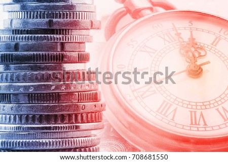 Time is money, time value of money concept : Coins and vintage brass pocket watch, idea of time which is a valuable commodity or resource and it's better to do work or things as quickly as possible. #708681550