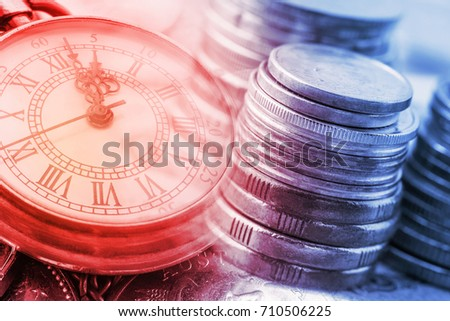 Time is money, time value of money concept : Coins and vintage brass pocket watch, idea of time which is a valuable commodity or resource and it's better to do work or things as quickly as possible. #710506225