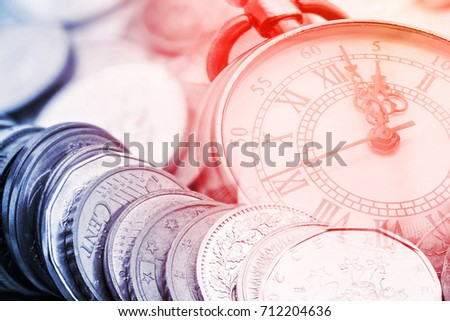 Time is money, time value of money concept : Coins and vintage brass pocket watch, idea of time which is a valuable commodity or resource and it's better to do work or things as quickly as possible. #712204636