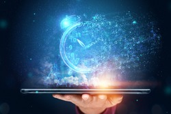 Time management concept, Hand close-up and a tablet with a hologram clock dissolving into air. Time is fleeting, dead line, the passage of time. Copy space