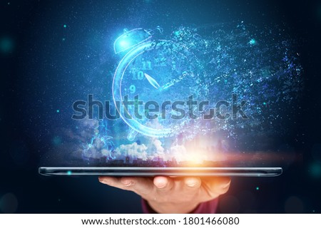 Time management concept, Hand close-up and a tablet with a hologram clock dissolving into air. Time is fleeting, dead line, the passage of time. Copy space Photo stock ©