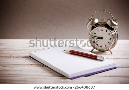 Time management concept: vintage alarm clock, pencil and notepad