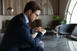 Time management. Serious male employee looking at wrist watch checking time waiting for hr invitation on job interview, punctual young businessman expecting partner who is late for meeting in office