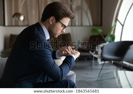 Time management. Serious male employee looking at wrist watch checking time waiting for hr invitation on job interview, punctual young businessman expecting partner who is late for meeting in office ストックフォト ©
