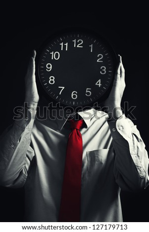 Time management with businessman holding clock in front of his head.