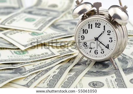 Time - money. Business concept. Analog hours on a heap of paper dollars