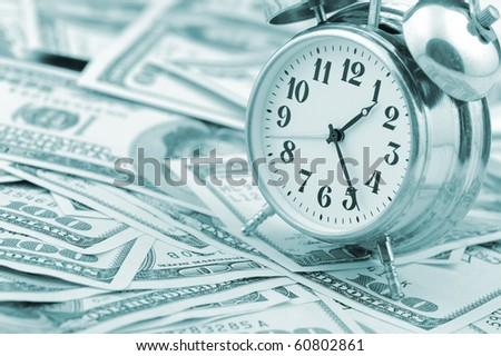 Time - money. Business concept. Analog hours on a heap of paper dollars. Blue tone