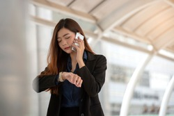 Time out concept. Urgent work, business woman seeing wrist watch and using mobile phone before meeting. Smart woman check the schedule before going to the office. Time out for appointment meeting.