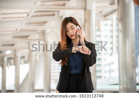 Time out concept. Urgent work, business woman seeing wrist watch and using mobile phone before meeting. Smart woman check the schedule before going to the office. Time out for appointment meeting Stockfoto ©