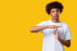 Time out gesture. Need break. Tired black teenager boy showing stop by hands looking at camera isolated on orange copy space. No racism. Pause message