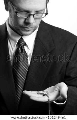 Time - This is a high contrast black and white image of a concerned businessman looking down at his pocket watch. Shot with a shallow depth of field. (Focus On Watch)