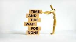 Time to action symbol. Wooden blocks with words time and tide wait for none. Beautiful white background. Businessman model. Business and time to action concept. Copy space.
