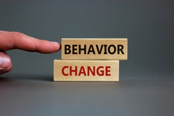 Time to behavior change symbol. Wooden blocks with words 'behavior change'. Beautiful grey background. Businessman hand. Copy space. Business, psychology and behavior change concept.