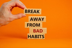 Time to break bad habits. Wooden blocks with words 'break away from bad habits'. Male hand. Beautiful orange background, copy space. Business and psychological concept.