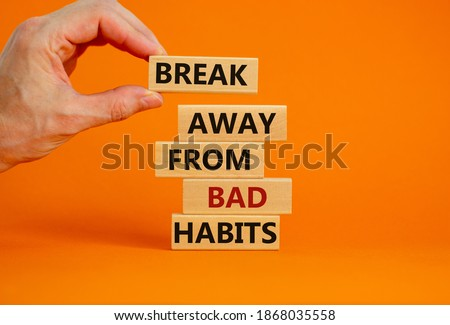 Time to break bad habits. Wooden blocks with words 'break away from bad habits'. Male hand. Beautiful orange background, copy space. Business and psychological concept. Stockfoto ©