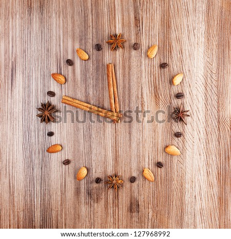 Time to cook. Clock face on a wooden background of almonds and coffee beans with arrow of cinnamon sticks.