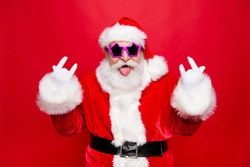 Time to dance on heavy metal disco music! Mature grandfather Santa in costume glasses with playful mood fooling around show tongue out make rock n roll sign isolated december noel red background