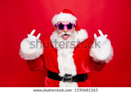 Time to dance on heavy metal disco music! Mature grandfather Santa in costume glasses with playful mood fooling around show tongue out make rock n roll sign isolated december noel red background #1190681263