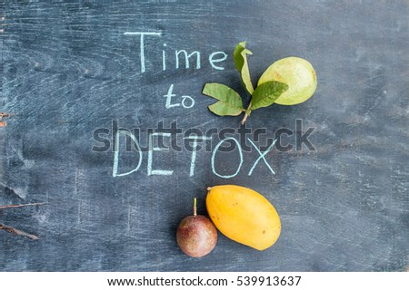 TIME TO DETOX chalk inscription on the wooden table fruits: mango, passion fruit and guava. Health Concept.