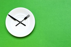 Time to eat and diet concept, plate as a clock on the green background. Place for text.